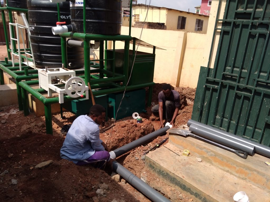 Two men lay a pipe in a trench, in front of the biodigester.