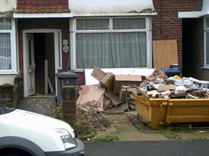 A house with a full skip outside, on the driveway