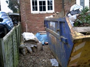 a full skip and a heap of sandbags outside a house