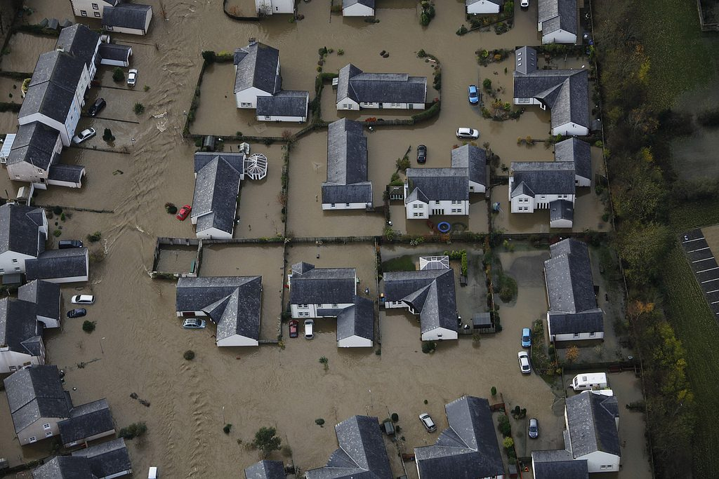 Aerial shot of small modern housing estate engulfed in flood water