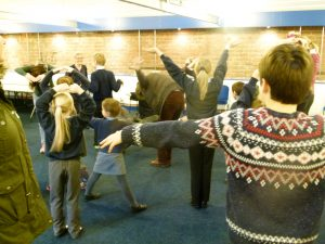 children and adults freeze in a shape in a warm up activity