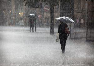 two figures walk through the rain, holding umbrellas.