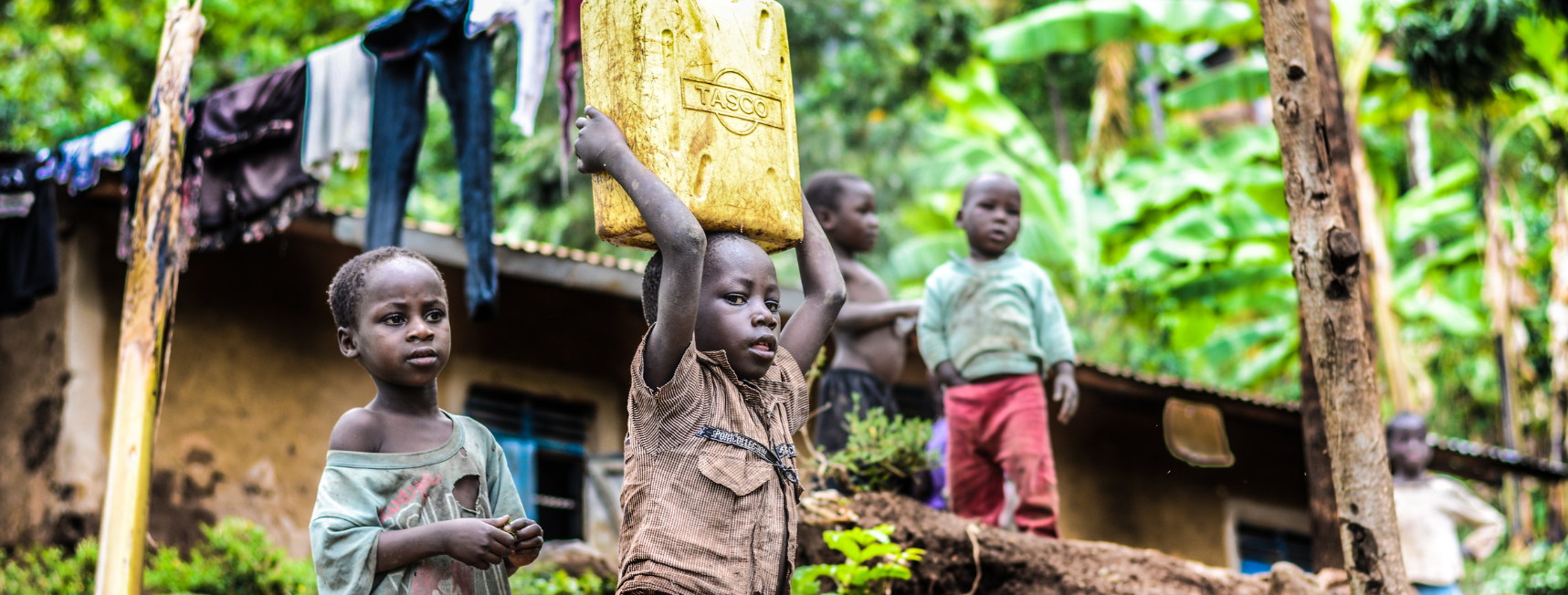 An image of a child carrying a bucket of water above their head. The child appears to live in poverty and in stood infront of a 'slum' with several friends.