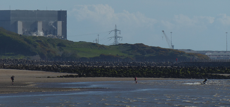 Heysham powerstation next to beach and sea, in which people are doing watersports
