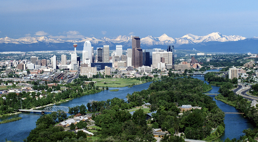 A cityscape image of Calgary with snow covered rockies in the distance