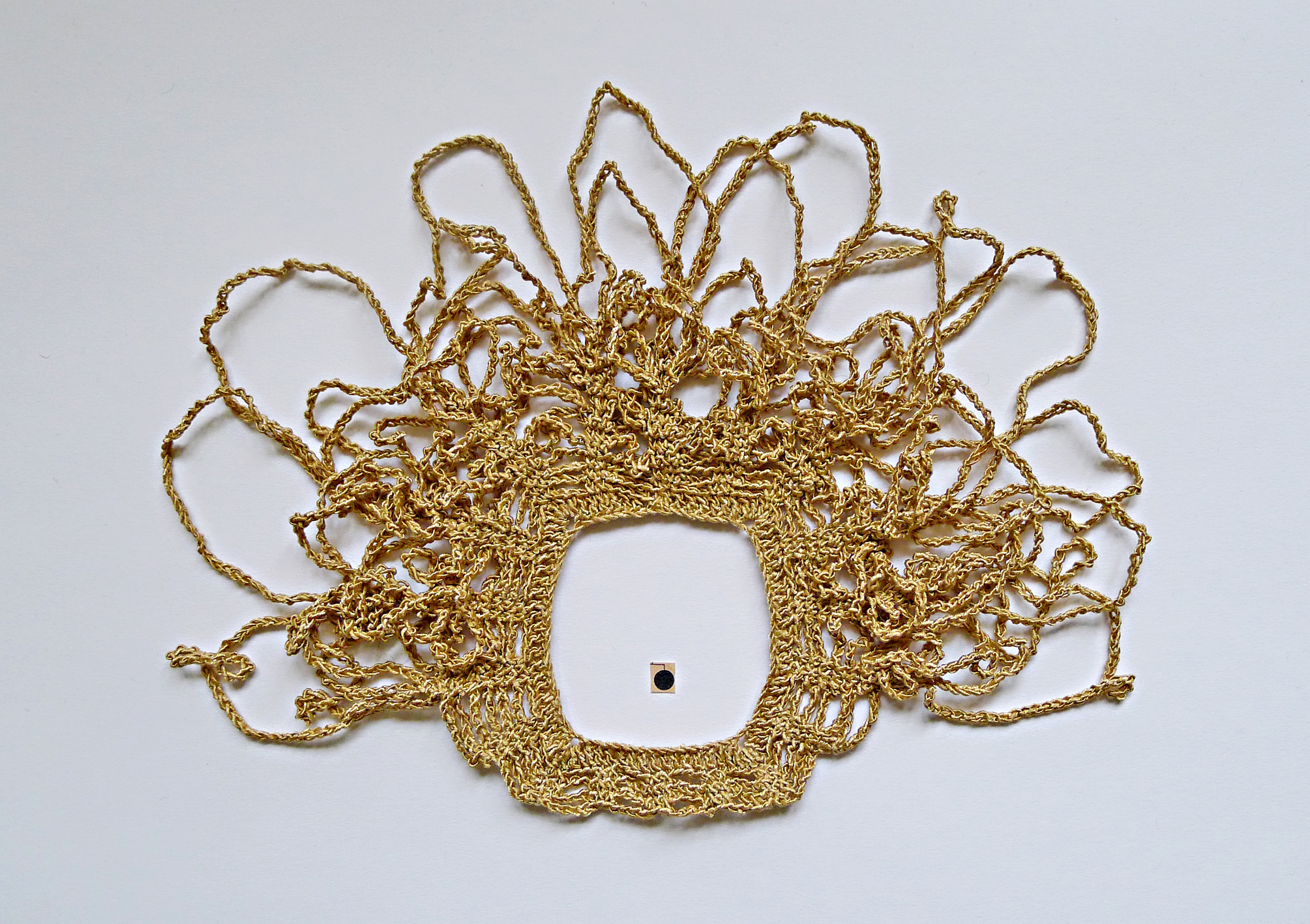 A small crochet work, of a shiny ochre hue, is laid out on a piece of white paper.