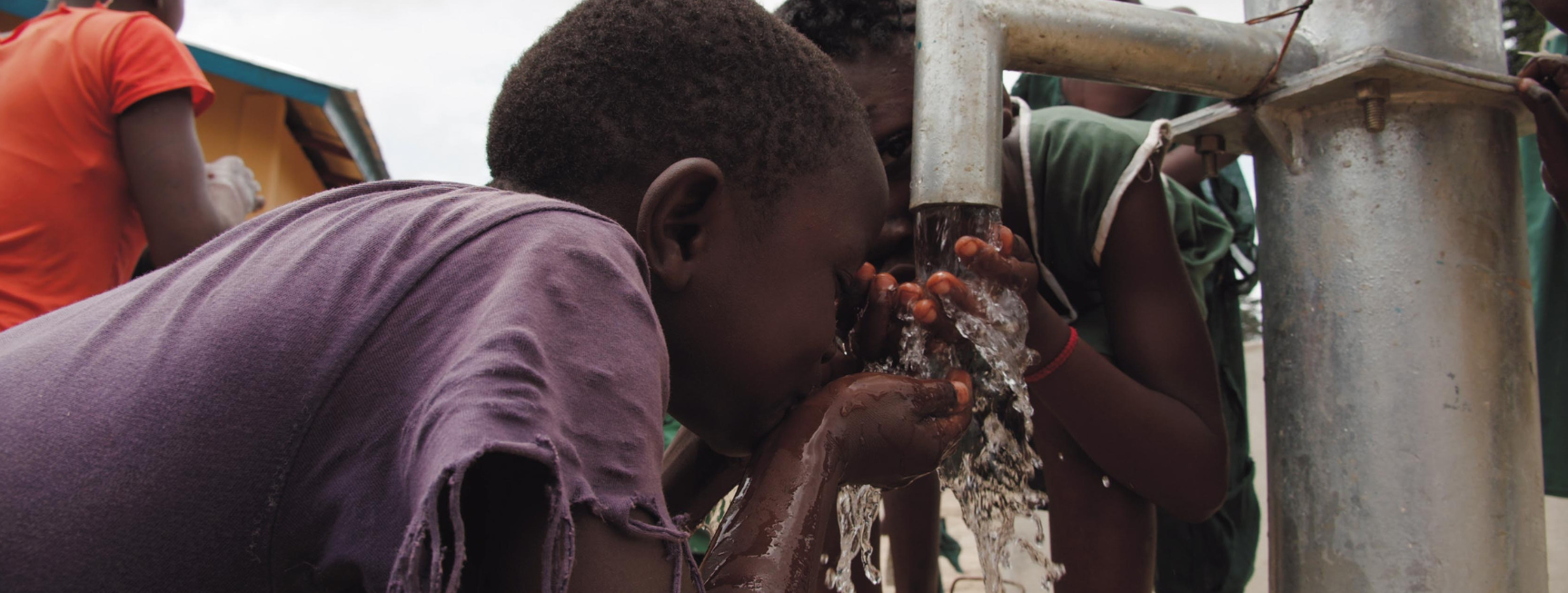 An image of an African child drinking clean water from a water pump. The child is cupping their hands together and bringing the water to her mouth.